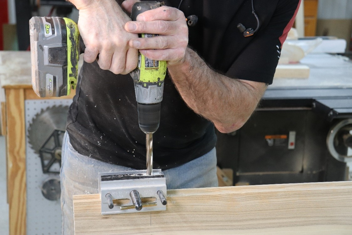 Drilling the hole with the dowel jig in place