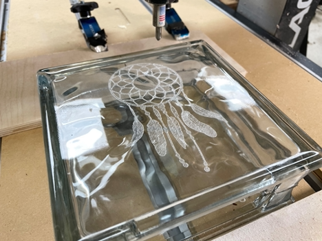 Finishing the glass engraving after running the CNC