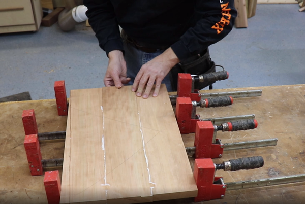 Finalizing wood panel by gluing pieces together and clamping