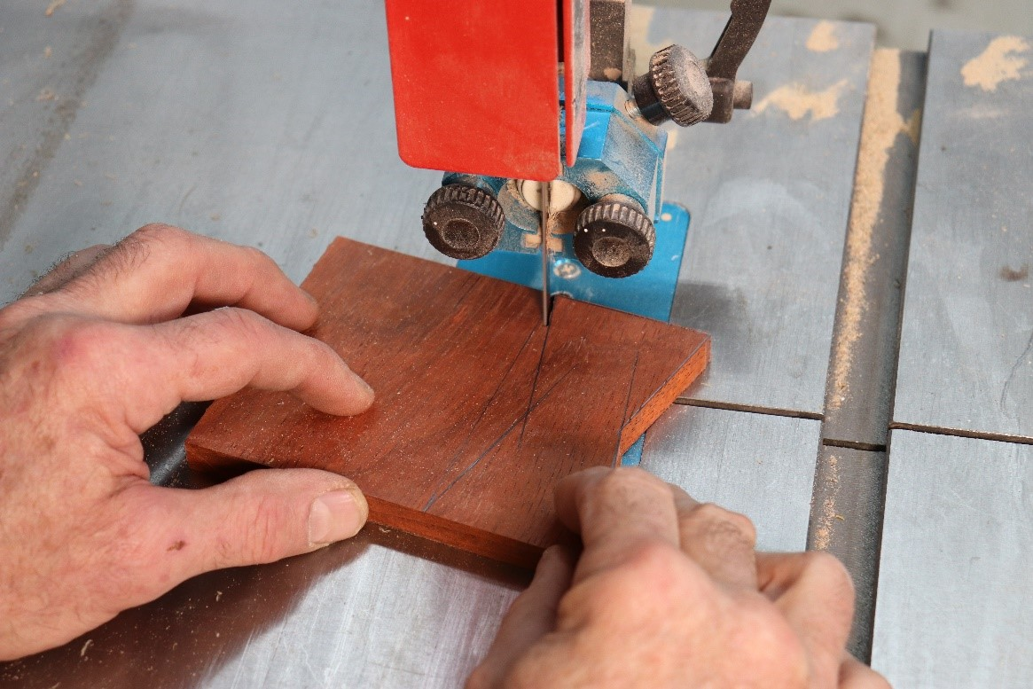 cutting out the wood with a vertical bandsaw