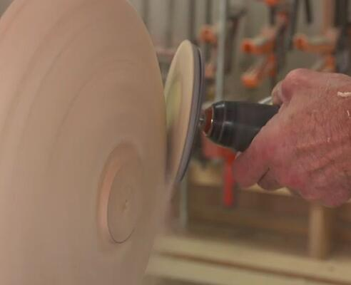 sanding the exterior shape of the wooden bowl