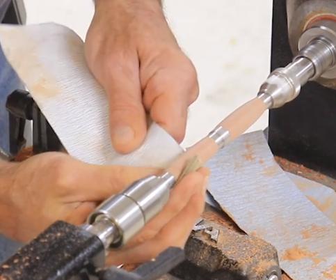 sanding the pen on the revo lathe