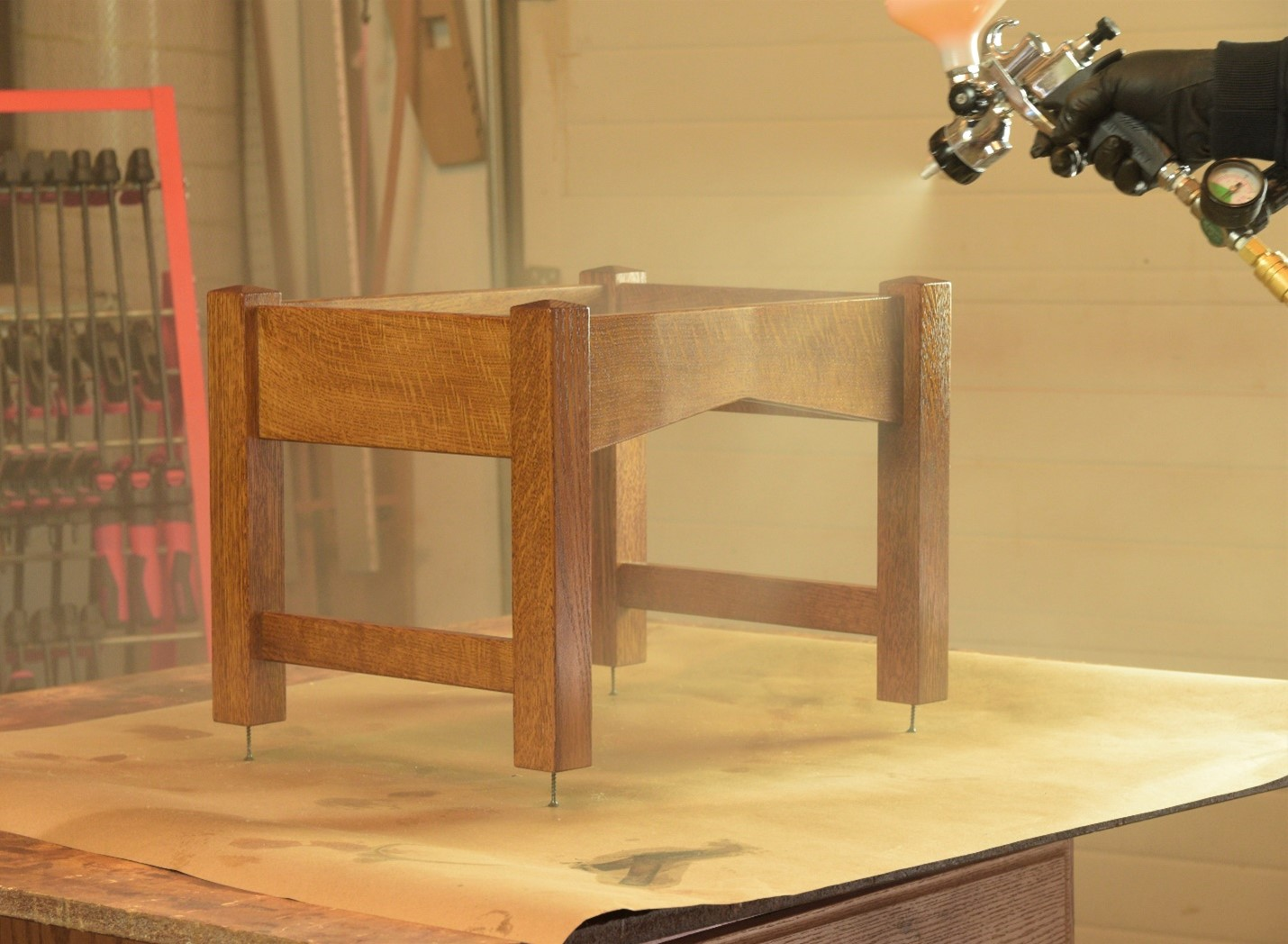 using a sprayer to get an even layer of choice of finish on wood